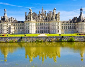 """Chambord, France - July 31, 2009: Great panoramic of Chambord Chateau reflected in the canal in a summer day with blue sky. There are some unrecognizable people in the balconies."""