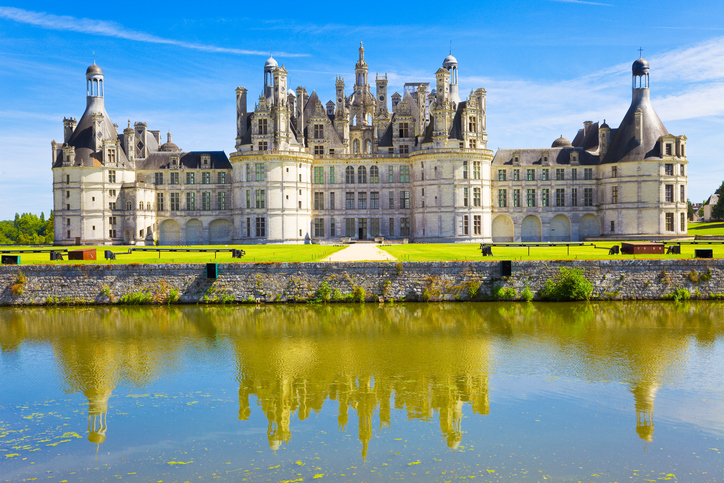 """""""Chambord, France - July 31, 2009: Great panoramic of Chambord Chateau reflected in the canal in a summer day with blue sky. There are some unrecognizable people in the balconies."""""""