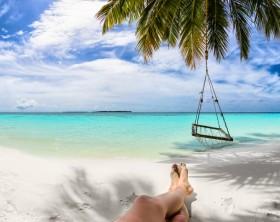 sandy feet on the beach under coco palm