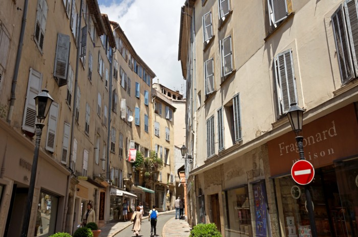 Grasse, France - May 3, 2013: Architecture of Grasse Town in the southern France. It is a city in the French department of Alpes-Maritimes. Grasse is famous for its perfume industry. The city was founded in the XI century. People go along street.