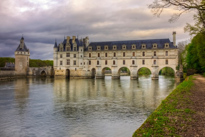 Chenonceaux, France- April 6, 2014: Image at the dusk in a cloudy evening of the Chenonceau Castle spanning the river Cher in the Loire Valley ,France.