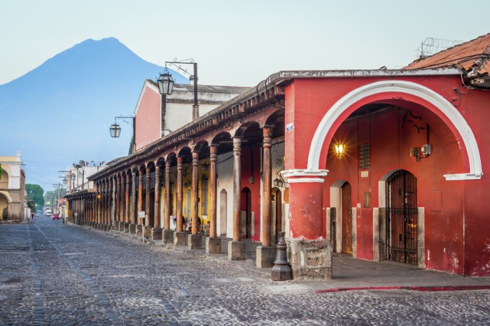 View of colonial buildings with prominent red archway in Antigua central park with view of 'Agua' volcano in background