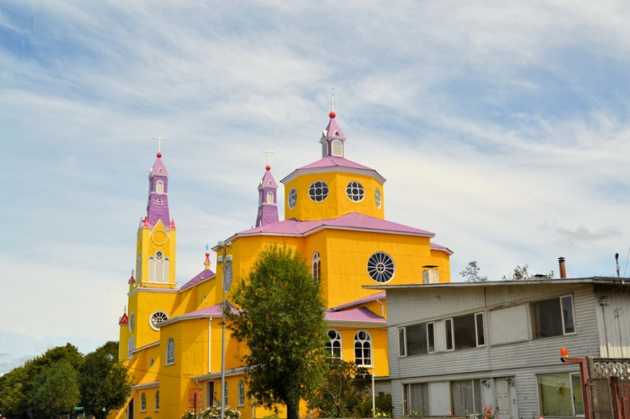 Bright yellow and purple painted facade of the historic Iglesia San Francisco in Castro, capital of the island of Chiloe in Chile