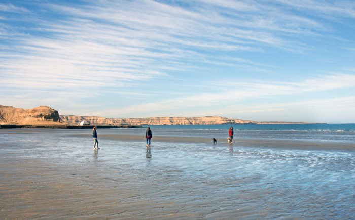 Puerto Piramides, Chubut, Argentina - August 20, 2014: three persons  and a dog making an early morning stroll on the beach at low tide; the day promisses to become a bright sunny day in mid-winter. The rocky coastline of Peninsula Valdes is visible in the back.