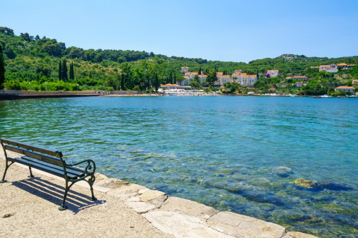 Kolocep, Croatia - June 27, 2015: Scene of the fishing port, village and beach, with locals and tourists, in the Kolocep Island, one of the Elaphiti Islands, Croatia