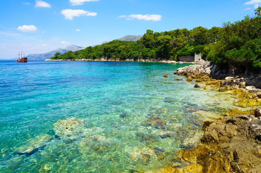 A rocky shore, boats and a ship, in the Kolocep Island, one of the Elaphiti Islands, Croatia