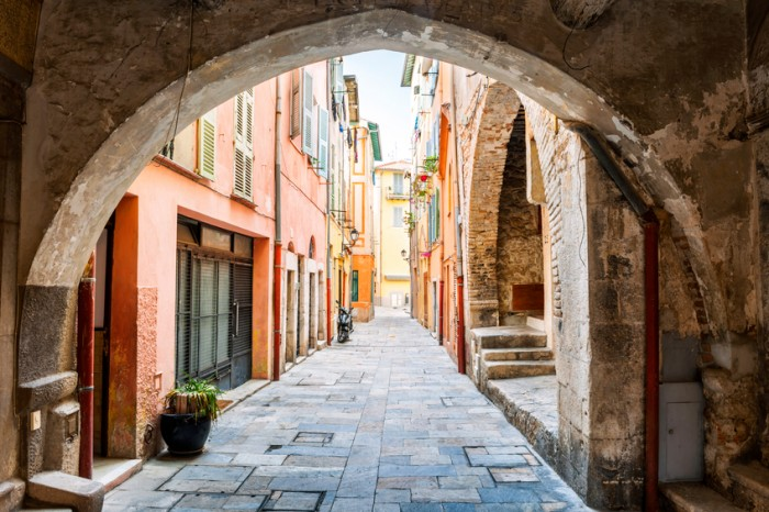 Narrow cobblestone street with colorful buildings viewed though stone arch in medieval town Villefranche-sur-Mer on French Riviera, France.