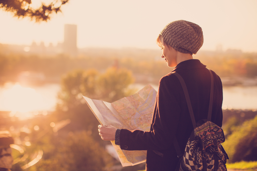 Young female traveler standing in front of beautiful city view and looking at the map