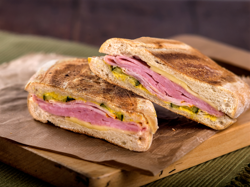 Toasted ham and cheese panini sandwich on wooden cutting board.