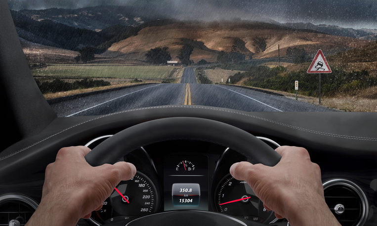 Driving in rainy weather. View from the driver angle while hands on the wheel. Alongside the road is a sign for slippery road. Rain splashed windshield.
