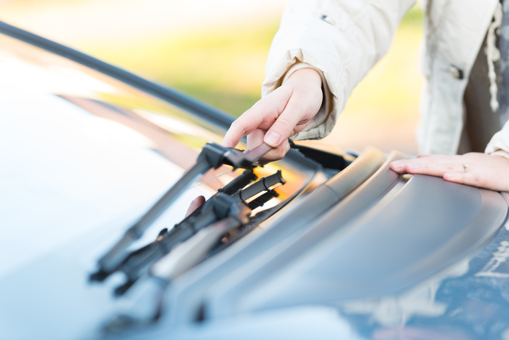 Woman's hand picking up windscreen wiper