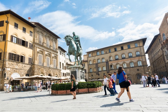florence,Italy-august 26,2014:tourist walking near the equestrian statue of Cosimo I de Medici made by Gianbologna in the piazza della signoria during a sunny day.
