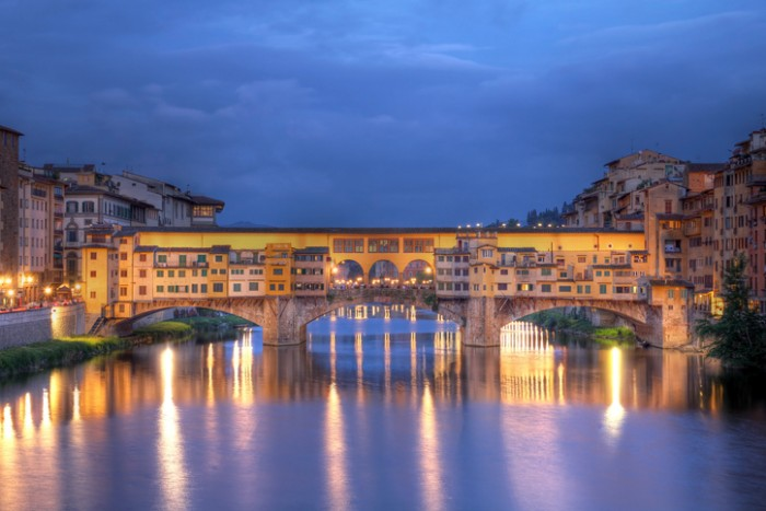 Famous Ponte Vecchio (Old Bridge) spanning over the Arno river in Florence/Firenze, Tuscany, Italy. HDR image taken at twilight time.