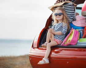 A little girl,a brunette with long curly hair,dressed in a striped sailor shirt,dark sun glasses,and a journey to the sea,sits in the trunk of the red car with clothes,suitcases and bags