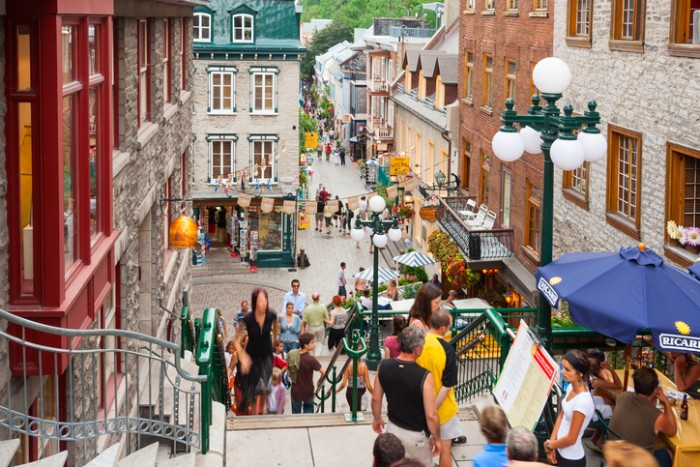 """Quebec City, Canada - July 28, 2006:  People walking past restaurants and store facades in the Petit Champlain neighbourhood of Quebec City, the oldest commercial district of North America."""