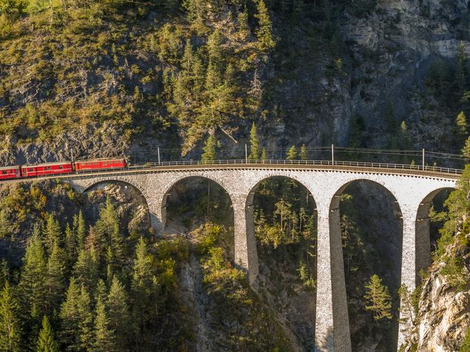 Train climbing on a breathtaking bridge in the Swiss Alps 1