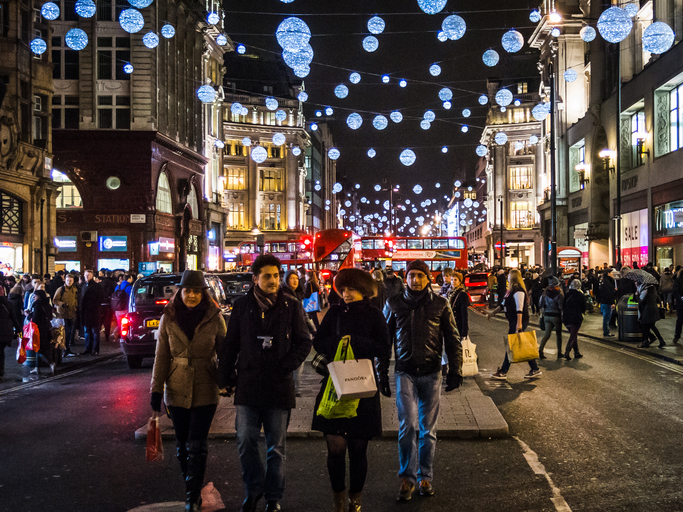 London, United Kingdom -  December 27, 2014: Group of friends walk and shop along Oxford Street, London, during Christmas time