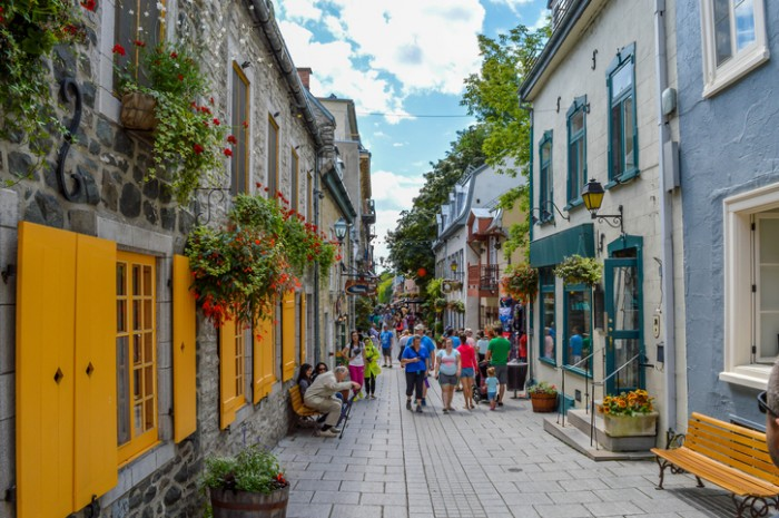 Quebec City, QC, Canada - 01 August, 2015: An elderly man stands up from the bench while other tourists are walking on the pedestrian street.