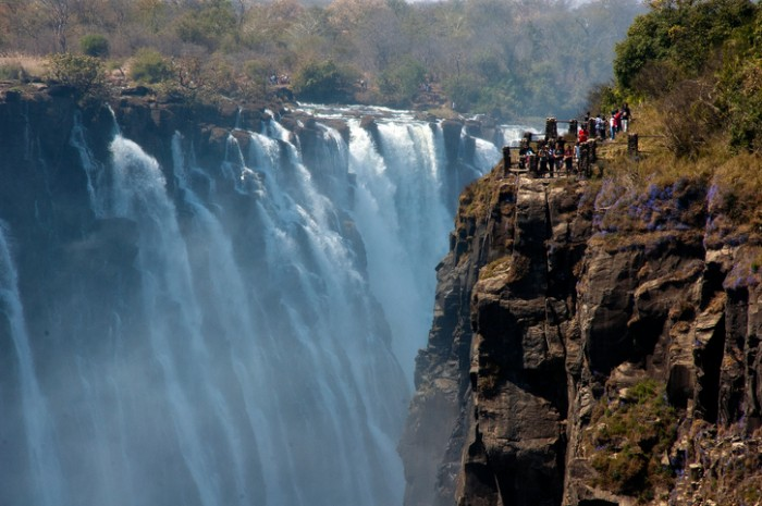 Victoria Falls, Zimbabwe - August 16, 2008: Tourists admiring Victoria Falls majestic beauty, zambezi river. The falls was discovered by David Livingstone in november 1855, Zimbabwe