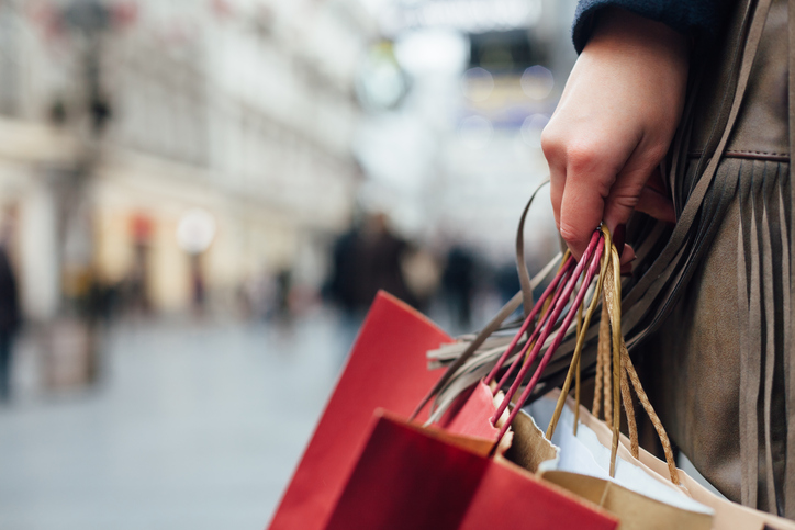 Closeup of woman holding shopping bags on the street with copy space