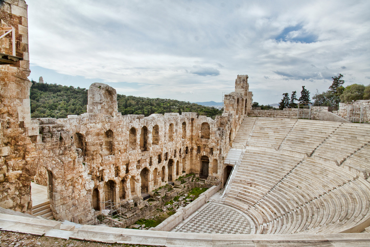 Remains of Odeon of Herodes Atticus  near the Acropolis of Athens. In the background could see Lombardy poplar trees and mountains.