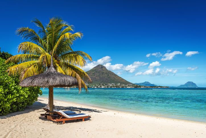Loungers and umbrella on tropical beach in Mauritius Island, Indian Ocean