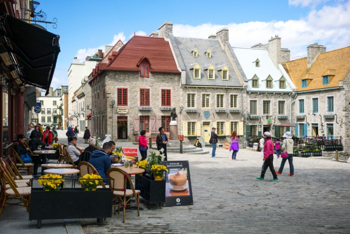 Quebec, Canada - May 5, 2014:  Tourists walking and seated in an open air bar of Royal square in the old town