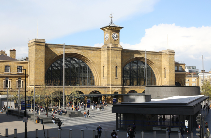 London, England - April 30, 2016: Kings Cross Railway Station London, a major London railway terminus basks in the afternoon sun. In the foreground, the new entrance to Kings Cross underground, on the concource, tourists and commuters sit and rest.