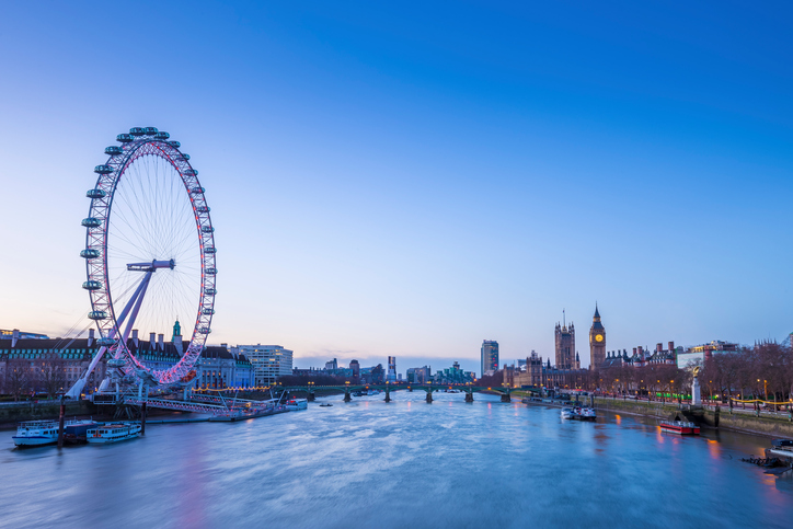 Skyline of London before sunrise with famous landmarks, Big Ben, Houses of Parliament, boat and clear blue sky - London, UK