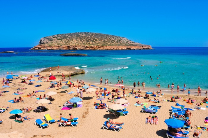 San Antonio, Spain - June 15, 2016: Sunbathers at Cala Conta beach in San Antonio, in Ibiza Island, Spain. Ibiza is a well-known summer tourist destination in Europe