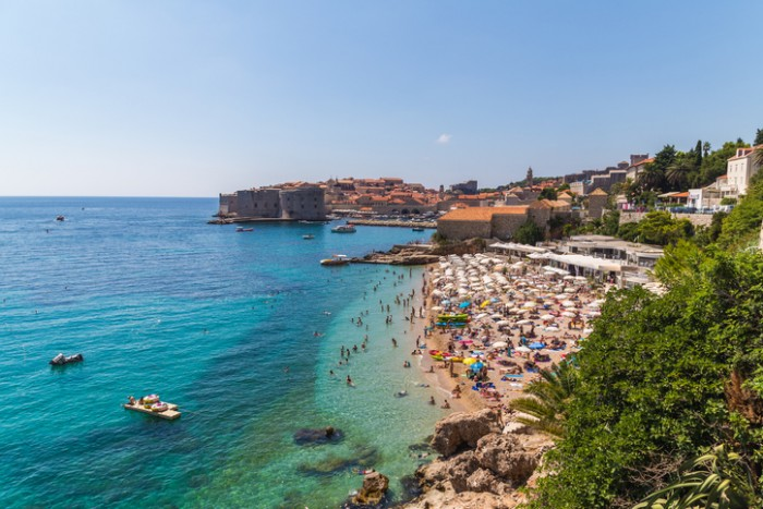 Dubrovnik, Croatia - August 10, 2016: A view of Banje Beach, the Adriatic Sea and Old Town in Dubrovnik during the day in the summer. Large amounts of people can be seen.