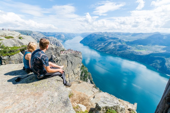 Stavanger, Norway - July 24, 2016: A young couple is sitting at the edge of a cliff at Preikestolen (Pulpit Rock) next to the city of Stavanger, Norway.