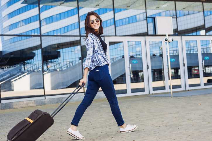 Young girl walking with luggage suitcase, active lifestyle and travel concept