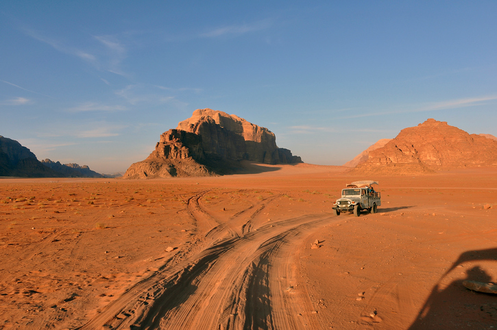 A caravan of jeeps in Wadi Rum Jordan are racing across the desert to get to a special place to see the sunset.