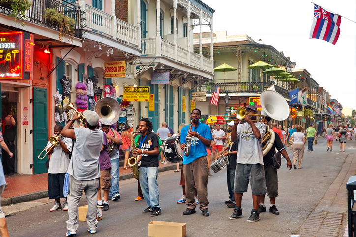 New Orleans, USA - August 7, 2013: In New Orleans on Bourbon St. on August 7, 2013 a jazz band plays jazz melodies in the street for donations from the tourists and locals passing by on this hot summer evening.
