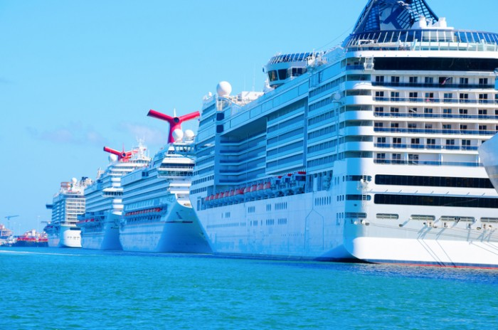 Miami, FL, USA - October 11, 2014: Row of big huge cruise ships lined up at the docks in Port of Miami recommissioning for the next cruise.