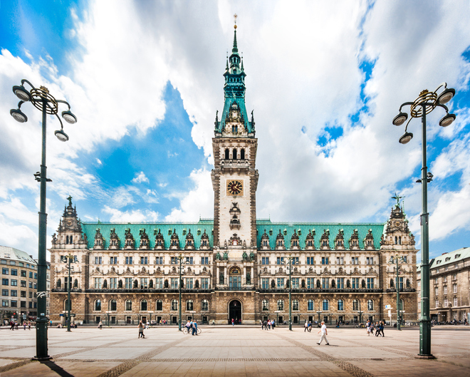Beautiful view of famous Hamburg town hall with dramatic clouds and blue sky at market square near lake Binnenalster in Altstadt quarter, Hamburg, Germany.