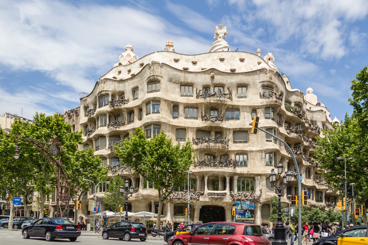 Barcelona, Spain - May 31, 2013: Street traffic and people in front of the famous Casa Mila or La Pedrera building