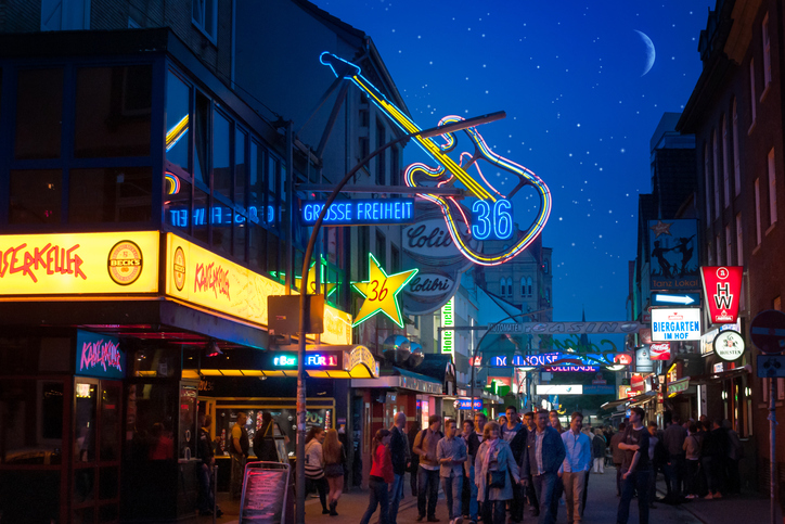 """Hamburg, Germany - June 15th, 2013: a group of tourists is visiting the nightly Reeperbahn. They are walking along the famous street """"Große Freiheit"""", where the Beatles became well-known at the star-club in house number 36."""