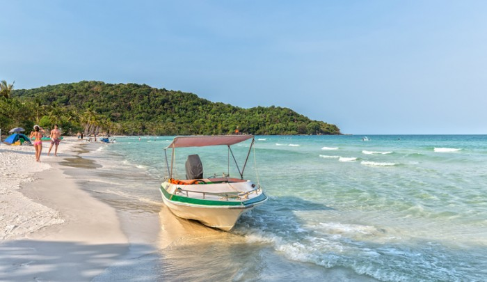 Phu Quoc, Vietnam - April 9th, 2015: The canoe on beautiful beach with the waves lapping against the boat thoroughly, so far as the couple badminton Guests enjoy a weekend together on the island pearls beautiful Phu Quoc, Vietnam