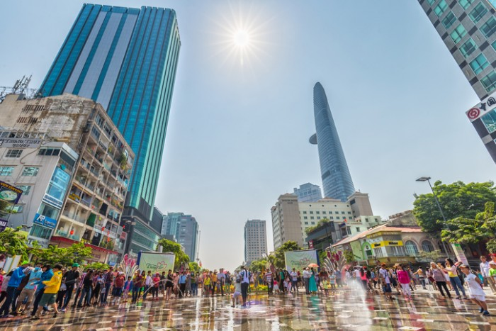 Ho Chi Minh City, Vietnam - February 10th, 2016: Sunny spring street walk with hundreds people in costume gathered on a beautiful pedestrian welcome spring, so far skyscrapers symbolize growth development country in Ho Chi Minh city, Vietnam