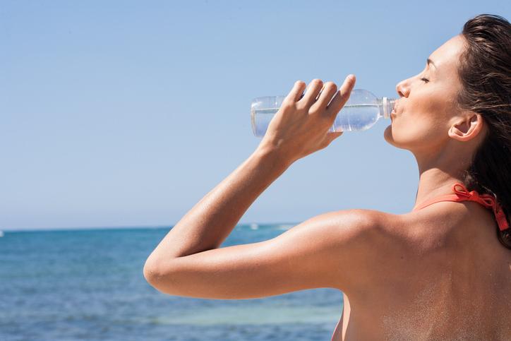 femme de dos qui boit de l'eau à la mer