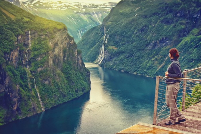 young woman looking at beautiful mountain landscape of Norway with waterfall
