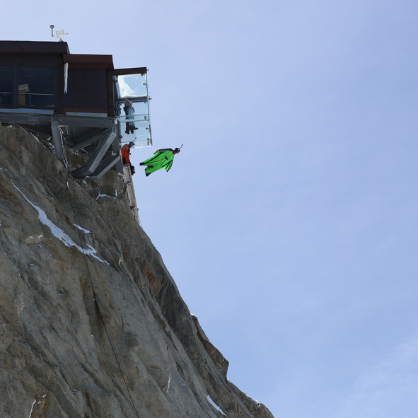 """Chamonix-Mont-Blanc, France - May 20, 2016: A BASE Jumper in Wingsuit jumps from the Top of Aiguille de Midi (3842m). Beside a Couple in the new """"Step into the Void"""" and other Tourists."""