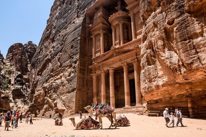 Petra, Jordan - 29 June, 2015: Camels resting in front of the Treasury in Petra Jordan. A family holding hands walking away.