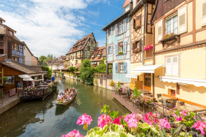 Collar, France- July 13, 2015: Tourist riding boat along canal in Colmar, Petit Venice, Alsace, France. The town is situated along the Alsatian Wine Route and considers itself to be the capital of Alsatian wine.