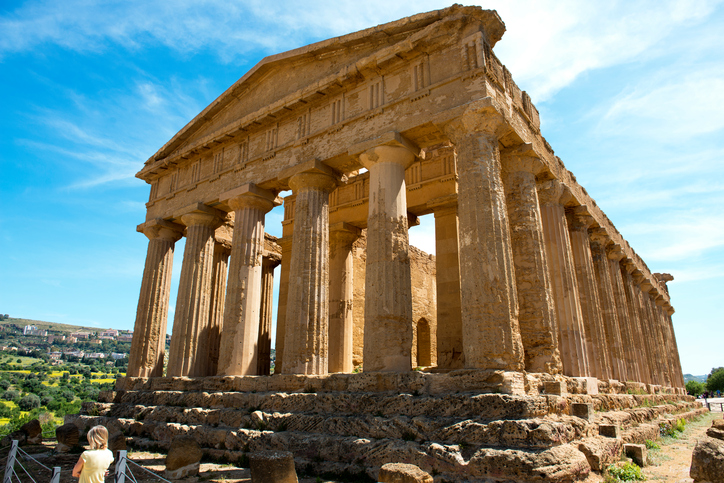 Agrigentp, Sicily, Italy - May 1, 2015: The ruins of The Temple of Concorde, Valley of Temples, Agrigento, Sicily, Italy with one person in the foreground
