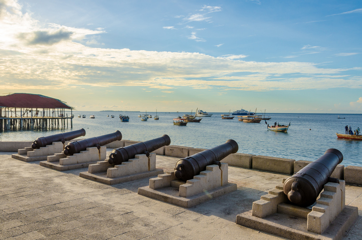 Five cannons lined up on the waterfront in Stone Town Zanzibar. Many fishing boats are out in the blue ocean. It's a nice summer evening day with a few clouds in the sky and calm ocean.