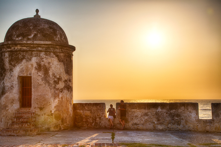 Cartagena, Colombia - February 24, 2014: Tourists and local residents watch the sun set over the caribbean sea from the old city wall surrounding Cartagena.