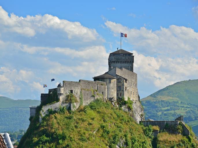 Lourdes, France - July 07 2012: An ancient castle dominates on the green rock above the famous town Lourdes.